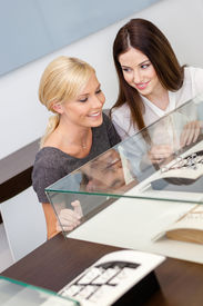 picture of jewel-case  - Two girls looking at window case with jewelry at jeweler - JPG