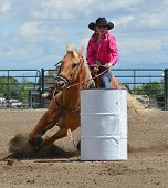 picture of barrel racing  - Beautiful young cowgirl riding around a barrel on a palomino horse.