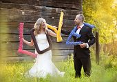 pic of bridal veil  - Happy bride and groom on their wedding day having fun with love cushions outside in the garden - JPG