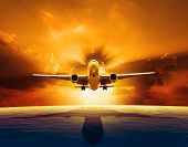 pic of water jet  - passenger jet plane flying over beautiful sea level with sun set sky above - JPG
