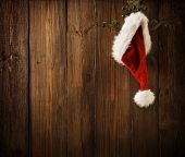 picture of santa claus hat  - Christmas Santa Claus Hat Hanging On Wood Wall Xmas Concept Decoration Over Grunge Wooden Background - JPG