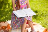 stock photo of little girls photo-models  - Closeup photo of girl in pink dress reading big book at park - JPG