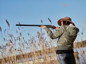 pic of shotgun  - Waterfowl hunting female hunter use the shotgun reeds and blue sky on background - JPG