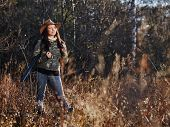 foto of hunter  - Waterfowl hunting the female hunter carry a shotgun and she use a duck call autumnal bushes on background - JPG