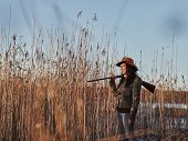 stock photo of shotguns  - Waterfowl hunting female hunter carry a shotgun reeds and blue sky on background  - JPG