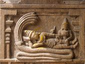 stock photo of lakshmi  - An ancient granite wall mural of the supreme Hindu form of god, Vishnu - reclining on Ananta Sesha with Lakshmi Devi.