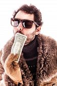 pic of scrooge  - a young man wearing a sheepskin coat isolated over a white background holding banknotes - JPG