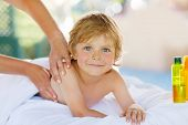 image of massage oil  - Adorable little blond kid relaxing in spa with having thai massage - JPG
