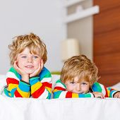 stock photo of indoor games  - Two little sibling kid boys having fun in bed after sleeping at home indoor - JPG