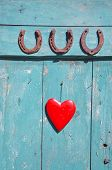 picture of horseshoe  - three old rusty horseshoe luck symbol and red heart on door - JPG