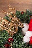foto of deer family  - Christmas decoration   like wicker iron deer at red and white candles  and fir branches  with selective focus - JPG