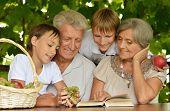 stock photo of grandparent child  - Grandparents with her grandson reading in summer at table - JPG