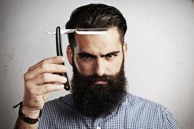 foto of hooligan  - Portrait of bearded man with vintage straight razor - JPG