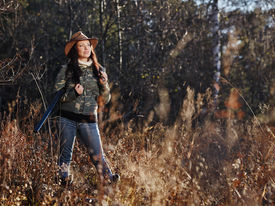 stock photo of shotgun  - Waterfowl hunting the female hunter carry a shotgun and she use a duck call autumnal bushes on background - JPG