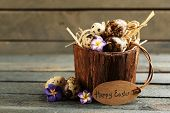 picture of bird egg  - Bird eggs in wooden bucket with decorative flowers on wooden background - JPG