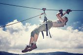 stock photo of sportive  - Active sportive woman hanging on the tightrope between mountains - JPG
