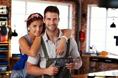 pic of hand drill  - Happy young caucasian couple standing at home workshop - JPG