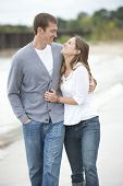 pic of barefoot  - A beautiful happy young caucasian couple smiling and walking barefoot on the beach. ** Note: Soft Focus at 100%, best at smaller sizes - JPG
