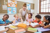 picture of pupils  - Pretty teacher helping pupils in classroom at the elementary school - JPG