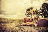 stock photo of hippy  - Romantic girl in a wreath of wild flowers travelling with her guitar - JPG