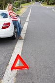 stock photo of annoying  - Annoyed young woman beside her broken down car in the street - JPG