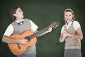 stock photo of serenade  - Geeky hipster serenading his girlfriend with guitar against green chalkboard - JPG