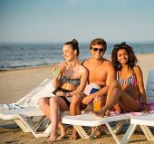 pic of sunbathers  - Group of multi ethnic friends sunbathing on a deck chairs on a beach  - JPG