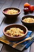 stock photo of crisps  - Three rustic bowls filled with baked plum and nectarine crumble or crisp photographed on dark wood with natural light  - JPG