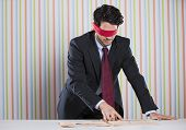 foto of blindfolded man  - Blindfold businessman reading the newspaper - JPG