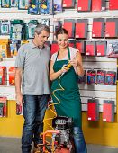 stock photo of air compressor  - Saleswoman explaining air compressor to male customer in hardware store - JPG