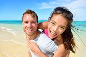 stock photo of multicultural  - Young couple having fun laughing on beach holidays - JPG