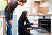 picture of showrooms  - Man and woman buying domestic kitchen in studio or furniture store showroom - JPG