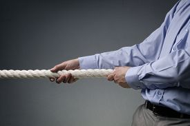 stock photo of roping  - Businessmen pulling tug of war with a rope concept for business competition - JPG