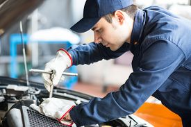 foto of overhauling  - Portrait of an auto mechanic at work on a car in his garage - JPG