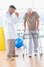 pic of zimmer frame  - Senior man on zimmer frame with therapist in fitness studio - JPG