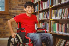 picture of wheelchair  - Portrait of little boy sitting in wheelchair at the library - JPG