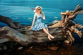 stock photo of driftwood  - Blonde girl in a hat and sun glasses sitting on driftwood on the riverbank - JPG