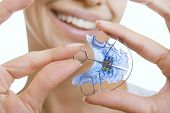 stock photo of crooked teeth  - Beautiful Smiling Girl Holding blue Retainer Braces for Teeth - JPG