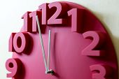 image of midnight  - Red clock showing five to midnight on the face  - JPG