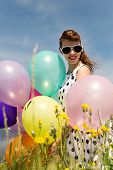 stock photo of suicide  - Attractive Rockabilly Girl with sunglasses and a suicide roll a dotted dress from the 50 - JPG