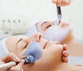 stock photo of face mask  - Use of a face mask to the face two young women in a beauty salon - JPG