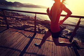 foto of crossed legs  - young fitness woman legs running on seaside wooden boardwalk  - JPG