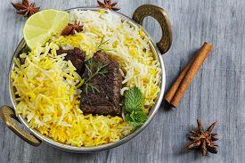 stock photo of raita  - Beef biryani in a kadai with basmati ruce and raita - JPG