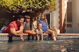 stock photo of hot water  - Outdoor shot of happy young family splashing water with hands and legs while sitting on edge of swimming pool - JPG
