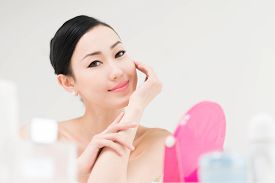 stock photo of mongolian  - Smiling Mongolian lady sitting at her dressing table - JPG