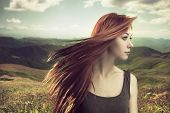 stock photo of wind blown  - beautiful girl upland with hair blown by wind - JPG