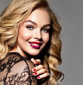 Blond smiling woman with long curly beautiful hair. Makeup. Fashion make-up. Fashionable girl dresse poster