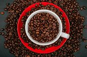 White Cup Of Coffee On The Red Plate With Roasted Coffee Beans On The Black Concrete Stone Backgroun poster