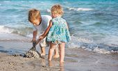 stock photo of children playing  - two children playing on sand beach - JPG