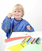 Young boy holding up a small brush with glue